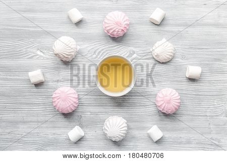 woman breakfast with cup of herbal tea and marsh-mallow on light wooden table background top view