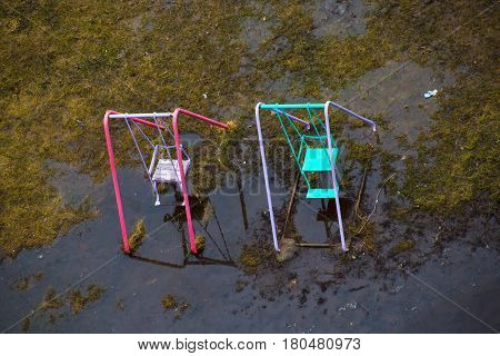 Swings Stand In A Water After Rain In The Spring