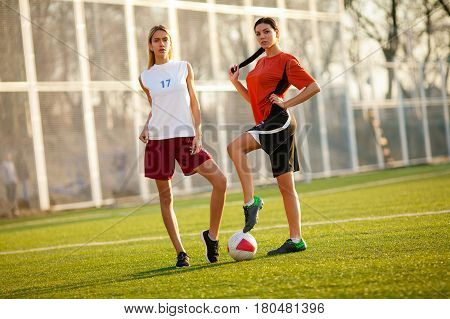 Two Girls In A Football Uniform, Stand On A Football Field With Ball.
