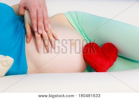 Couple expecting baby. Future mother lying on couch with red heart love symbol woman and man hands touching pregnant belly. Pregnancy parenthood concept.