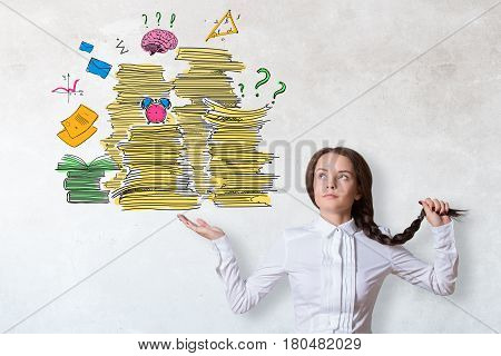 Pretty caucasian woman holding drawn paperwork pile on concrete background. Workload concept