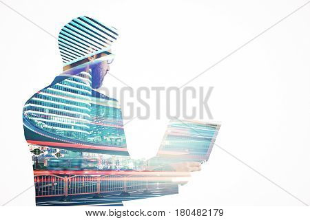 Side view of young businessman using laptop on abstract night city background. Technology concept. Double exposure