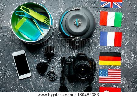Outfit of traveller with flags and plastic glasses on gray table background top view
