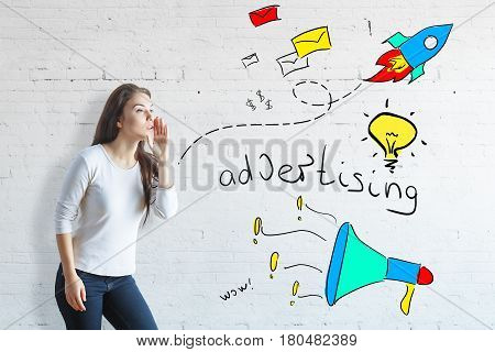 Side view of whispering woman on white brick background with colorful drawings. Advert concept