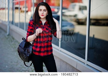 Fashion Portrait Girl With Red Lips Wearing A Red Checkered Shirt And Backpack Holding Sunglasses At