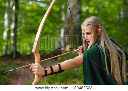 Beautiful female elf archer wearing green cape walking through the woods hunting with a bow and arrow ready to shoot danger protection defense fearless courage brave warrior fairytale fantasy costume.