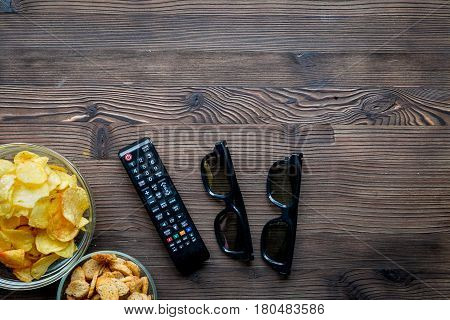 TV remote control and snacks on wooden desk background top view space for text