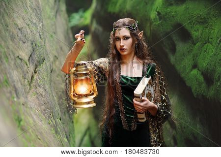 Attractive young long haired brunette female elf walking in the mysterious woods holding a lantern and an old book nature magic mystery cosplay creature mythical romantic fantasy innocence concept.