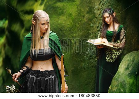 Beautiful young female archer elf standing in the woods dark haired female elf reading a book on the background copyspace warrior femininity friendship relationship fantasy cosplay film movie protect.
