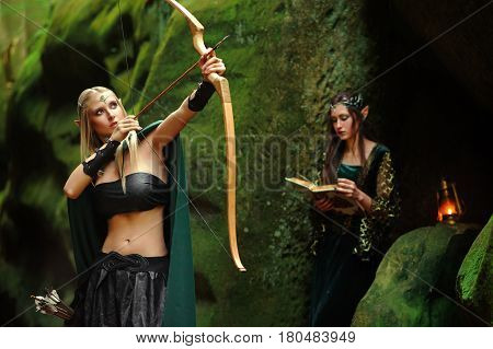 Two beautiful female elves wandering in a mysterious forest together hunting with a bow and arrows copyspace sisterhood relationship women femininity cosplay film actress character fairy hood princess.