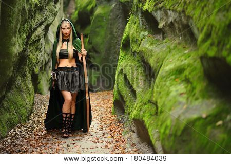 Full length shot of a beautiful blonde haired young woman elf wearing a green cape standing in the forest near an old rock copyspace weapon archer archery warrior myth legend hero costume sexy girl.