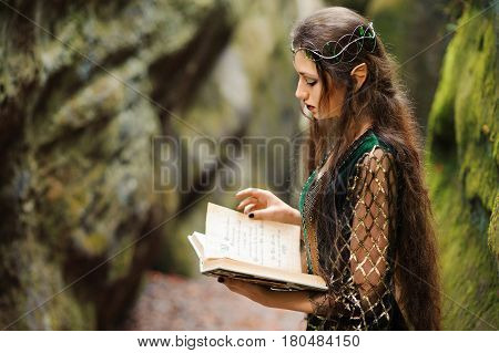 Horizontal shot of a beautiful young female elf with long wavy dark hair reading a book standing in the forest copyspace literature fantasy read books hobby knowledge myth fairytale creature heroine.