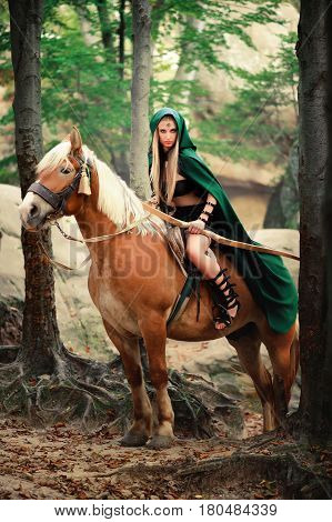 Vertical shot of a sexy brave female elf archer in a green cape riding her horse in the woods danger dangerous skilled fighter weapon armed mysterious forest hiding hunting costume character creature.