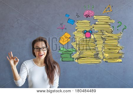 Pretty caucasian woman showing ok gesture on concrete background with drawn paperwork. Workload concept
