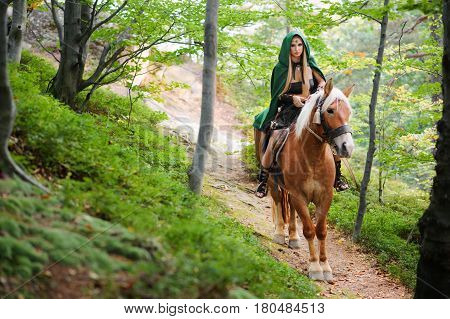 Young beautiful forest nymph in a green cape riding her horse on the path in the woods copyspace nature peaceful fairy tale mythical creature sexuality sensuality femininity rider cosplay fantasy.