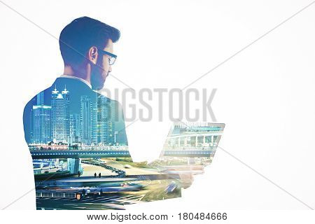 Side view of young businessman using laptop on abstract night city background. Business concept. Double exposure