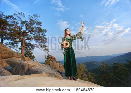 Full length shot of a beautiful woman elf wearing a green dress standing on top o f a mountain in the forest holding a book pointing away at the skies copyspace nature magical mystical character myth.