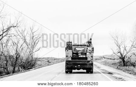 The rear end of an industrial truck loaded with pails and ladder travelling down a highway between rows of bare trees in black and white