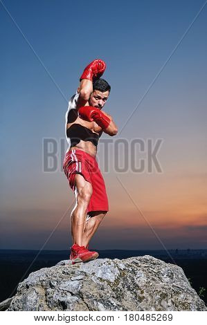 Full length shot of a handsome young male boxer wearing boxing gloves training outdoors sunset on the background fit toned body ripped muscles power masculinity lifestyle champion preparation concept .