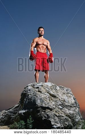 Young male boxer wearing boxing gloves looking to the camera confidently standing on top of a rock on sunset showing off his strong sexy muscular body power masculinity sport sportsperson lifestyle.