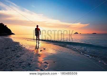 Lonely man walking on the tropical beach during amazing sunset. Perhentian islands Malaysia