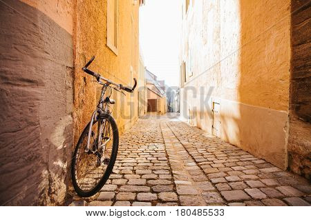 A Bicycle stands against the wall of the house on the streets of European cities. Conceptual image of a healthy lifestyle and environmental form of transport.
