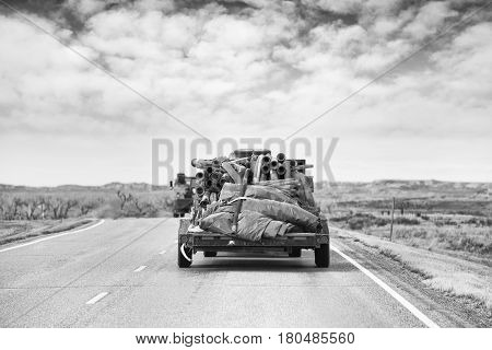 A flat bed trailer loaded with industrial hoses and tarps travelling down a highway in a black and white rocky landscape