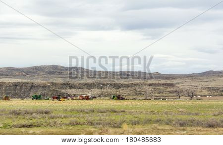 Various modern farming equipment parked in a pasture in a valley with mountains and hills in the background in Montana landscape