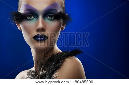 Space beauty. Horizontal portrait of a young woman wearing professional artistic makeup with feathers against blue background