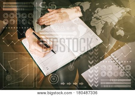 Top view of businesswoman's hand writing in organizer with abstract business charts and graphs. Accounting concept