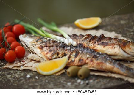 Grilled seabass with tomato, lemon and rosemary. Vintage table, outdoor.
