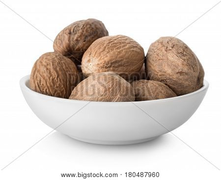 Nutmegs  in plate isolated on white background