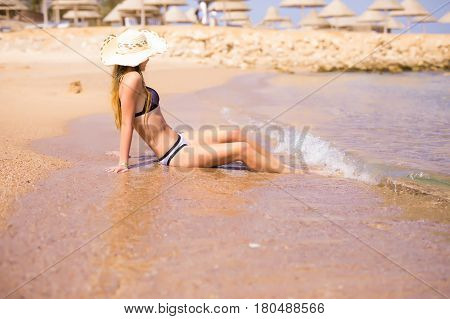 Woman In Swimsuit Sitting On The Beach And Looking The Horizon