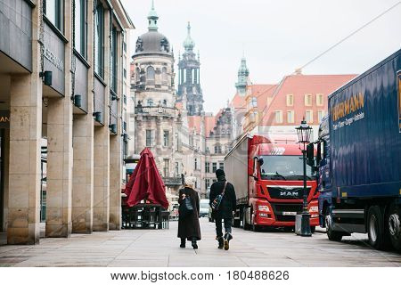 Dresden, Germany, 19 Dec 2016: Chinese tourists, a man and a woman are looking at the sights in the centre of Dresden.