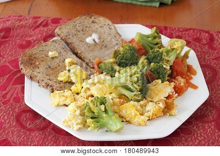 Octagon plate with breakfast food of scrambled eggs cooked with broccoli and tomatoes with buttered toast. Big breakfast of eggs vegetables and toast.