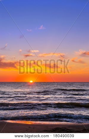 Warm summer night on sandy beach by sea. Sunset at Baltic sea in Lithuanian resort Palanga. Rays of sun shine through the low rare cirrus clouds. Tidal waves wash the sandy beach