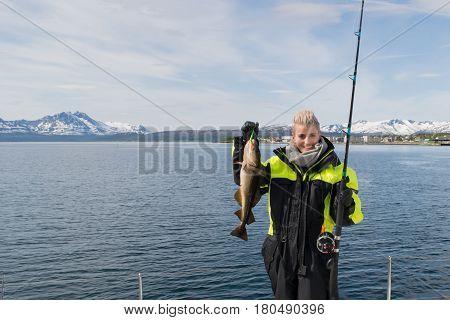 A beautiful girl fishing north of artic circle