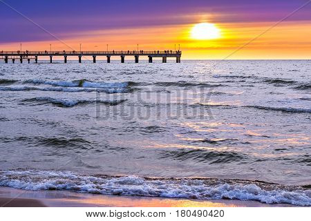 Sunset at Baltic sea in resort of Lithuania Palanga. Rays of sun shine through the low rare cirrus clouds. Pedestrian pier extends into the sea. Tidal waves wash the sandy beach