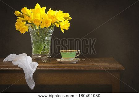 Still life with antique glass vase filled with spring daffodils on rustic table
