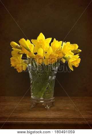 Bunch of spring daffodils in an antique glass vase sitting on rustic table