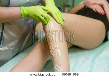 Sugaring Sugar waxing feet in the beauty salon. Depilation of the feet