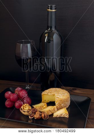Soft washed-rind cheese hazelnuts walnut red grape and wine in the glass and bottle