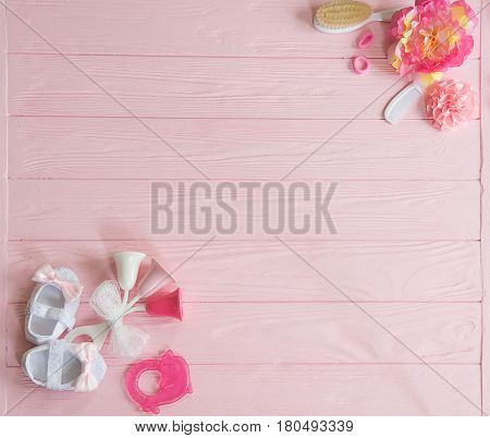 A newborn baby girl background. Newborn accessories for a baby girl on a pink wooden background.