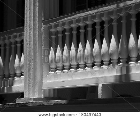 The balusters of a colonial style balcony in Charleston, South Carolina form an abstract repetition of shapes and shadows