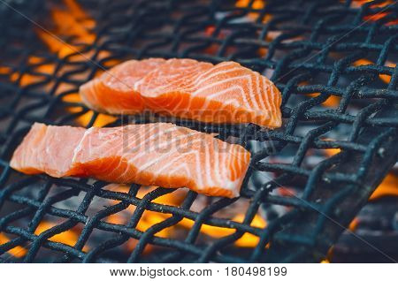 Grilled salmon steaks on a grill. Fire flame grill. Restaurant and garden kitchen. Garden party. Healthy dish.  Raw meat and sunlight