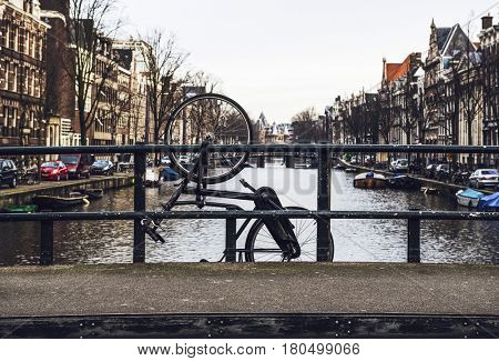 Old broken bicycle hanging off bridge tied to railing on canal of Amsterdam, Netherlands