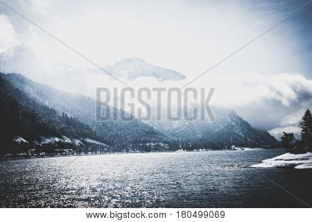 Freezing cold alpine lake in a winter landscape with a backdrop of snowy forested peaks obscured by low lying clouds