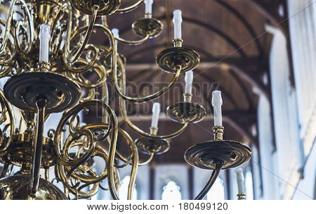 Partial view of an elaborate curling brass chandelier with multiple arms converted to electricity hanging from the vaulted wooden ceiling of a church