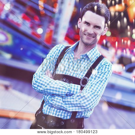 Single handsome young man dressed in traditional German suspenders with folded arms at carnival