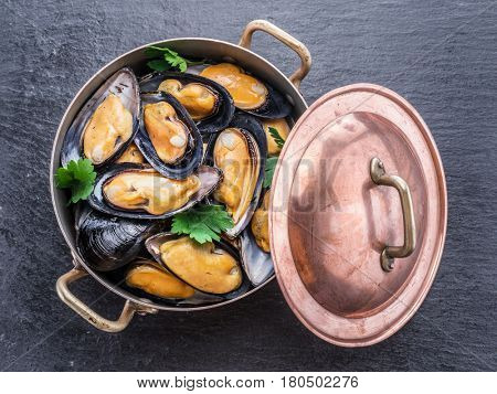 Boiled mussels in copper pan on the graphite background.